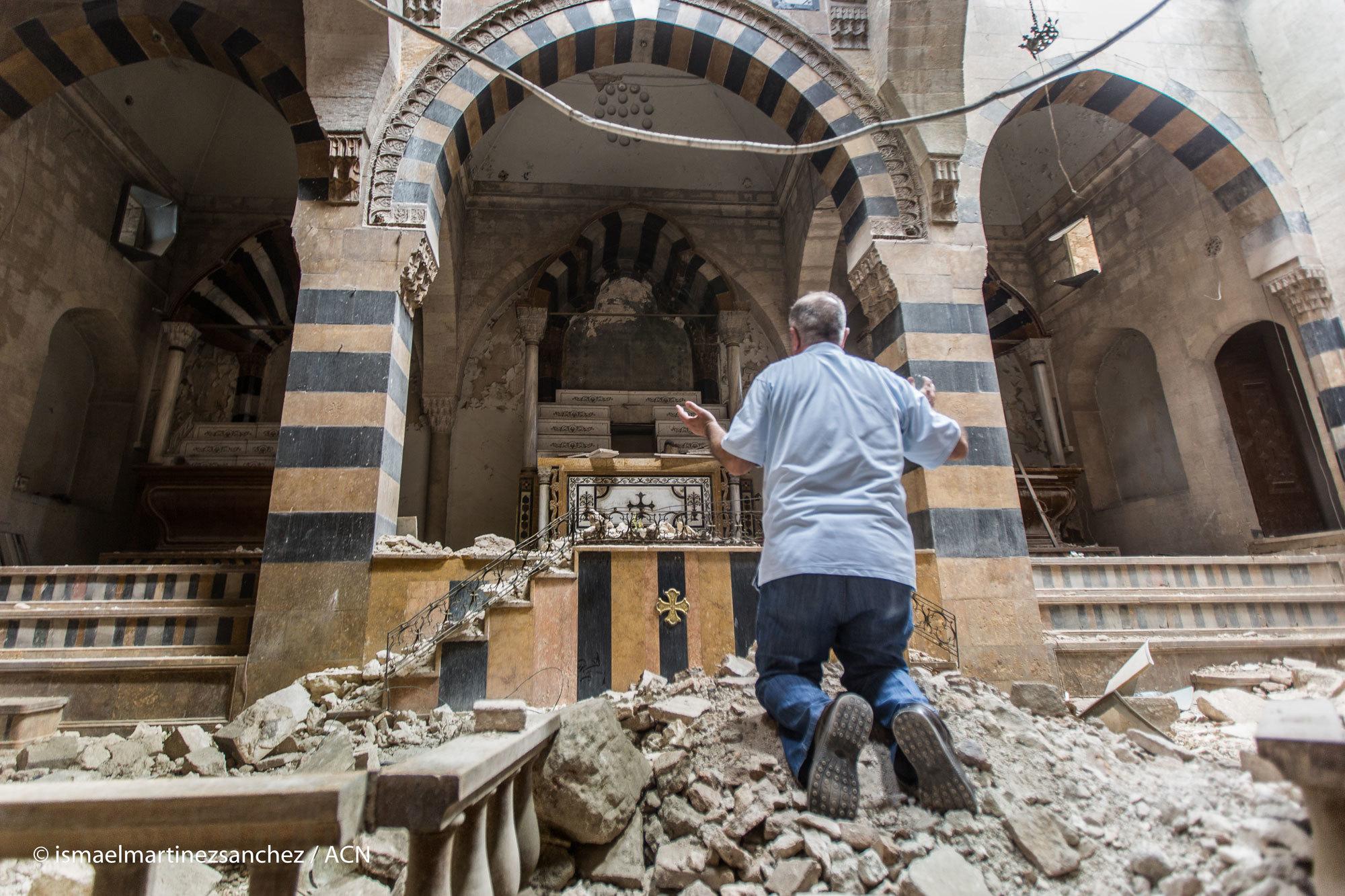 Ein Mann betet in einer zerstörten Kirche in Syrien C KIRCHE IN NOT Ismael Martinez Sanchez
