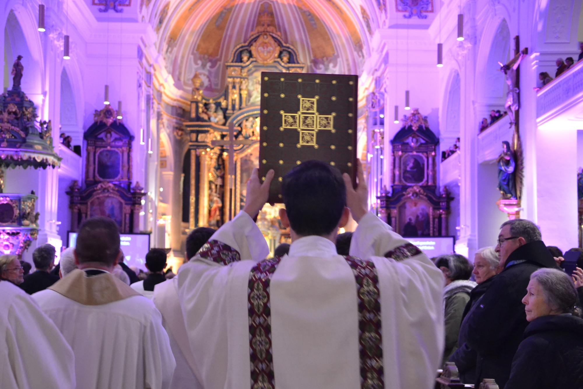 2019-ueber-den-boten-priester-mit-evangelienbuch-in-der-basilika